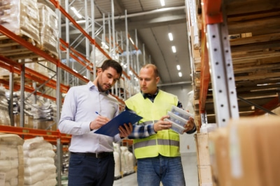 worker-and-businessmen-with-clipboard-at-warehouse